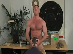 Horny gay swallows cock in office