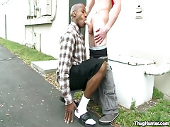 Dark stud greedily throats cock outdoor